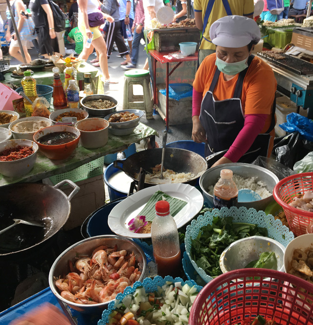 A woman wearing a face mask and cooking food in a round wok at the Chatuchak Market in Bangkok