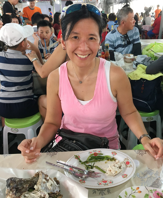 A woman in a pink shirt having a meal in a crowded outdoor dining area