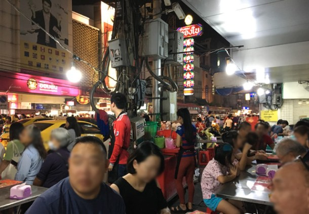 A crowd of people sitting next to a busy street in Chinatown, Bangkok