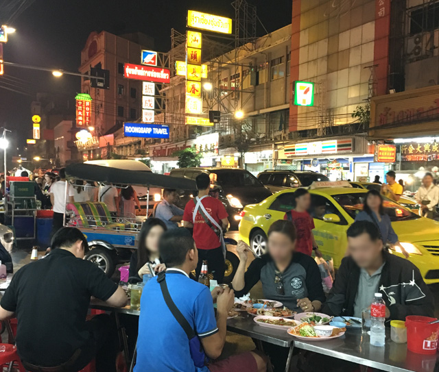 People dining at tables next to a busy road full of cars in Chinatown, Bangkok