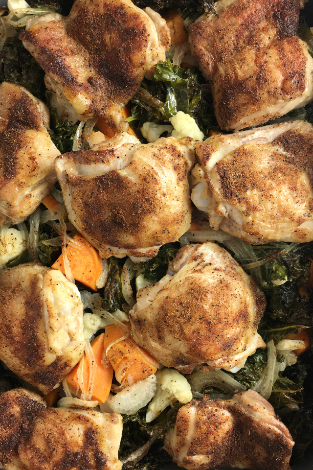 Close-up of a pan of roast chicken resting on a bed of roasted kale, onions, sweet potatoes, and cauliflower