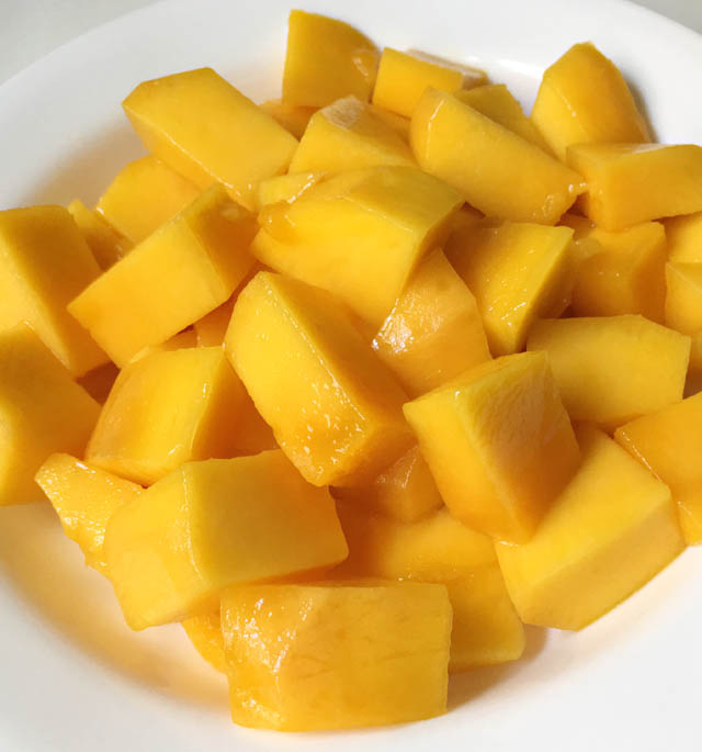 A white round plate containing cubed chunks of yellow orange mango