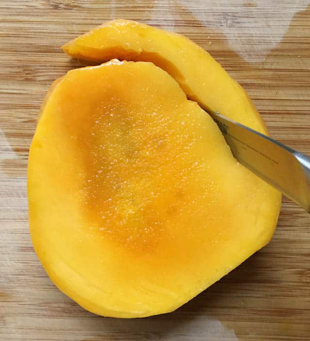 A knife cutting off a section of mango off the pit on a wooden cutting board