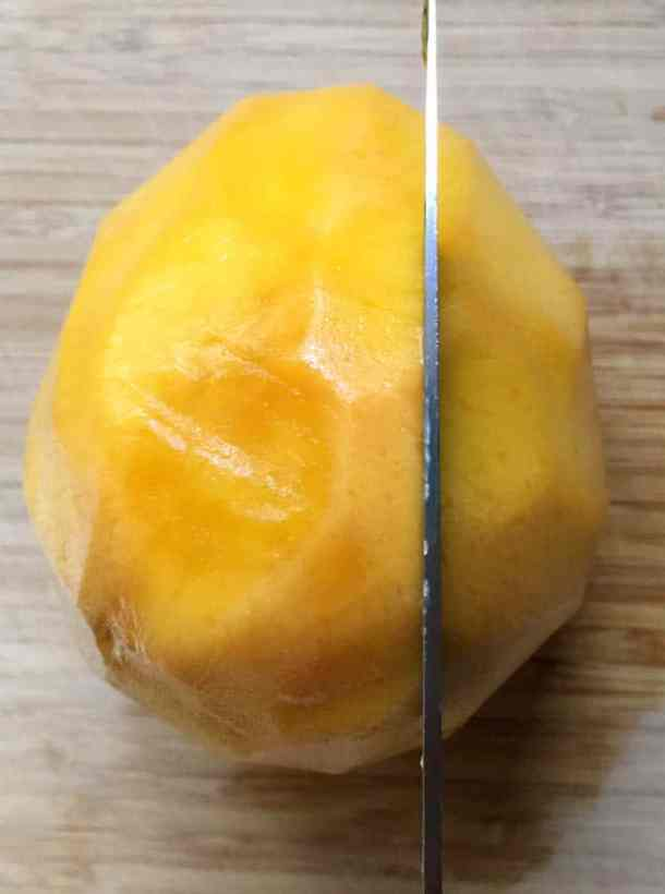A knife slicing into a large yellow orange mango on a wooden cutting board