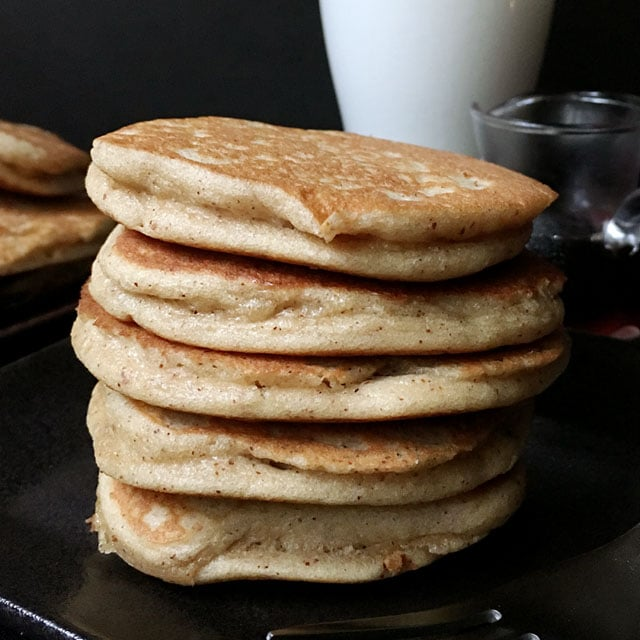 A stack of 5 brown pancakes on a dark plate, a glass of milk in the background