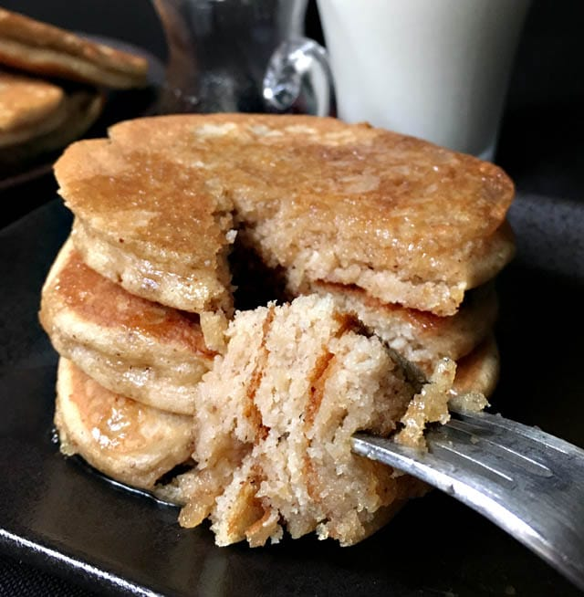 A forkful of pieces of pancakes from a stack of 3 brown almond pancakes on a dark plate