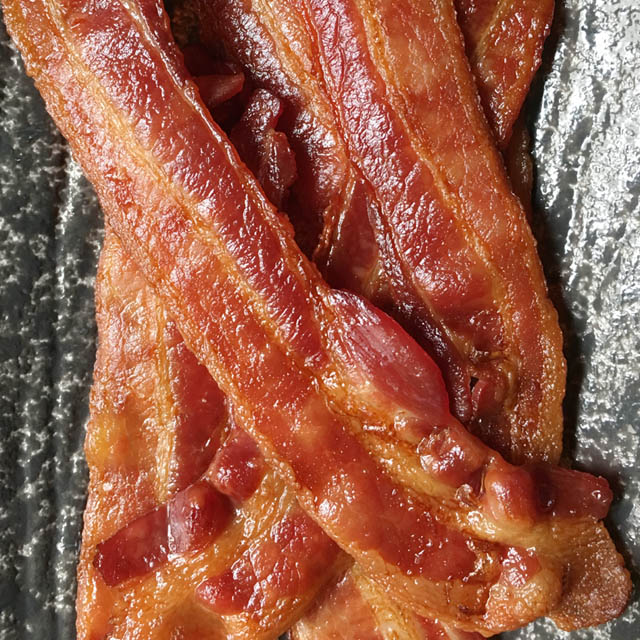 Several slices of cooked bacon for a crowd on a grey plate
