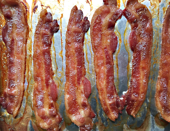 Six slices of cooked bacon on a foil-lined baking pan