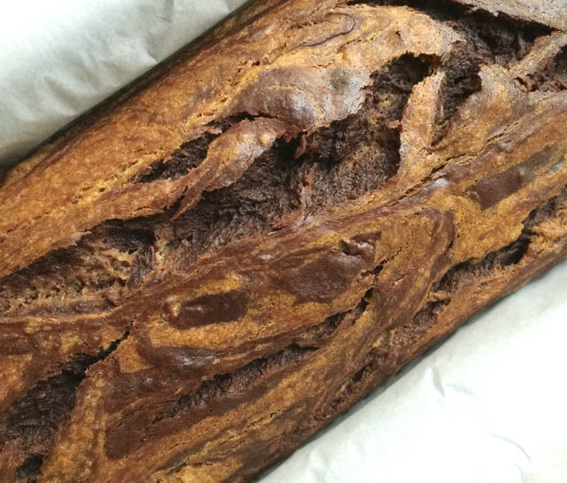 Close-up view of a brown chocolate swirl banana bread with swirls and cracks in the top.