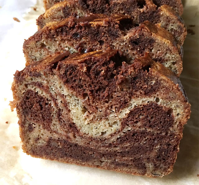 Slices of chocolate banana bread on a wooden cutting board