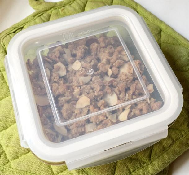 A square lid sealed food dish containing almond apple crumble, sitting on two green potholders
