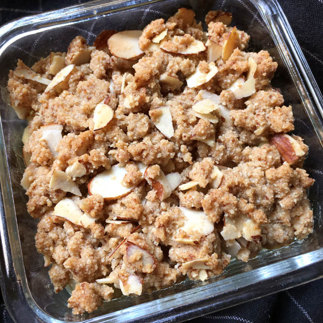 A square glass dish containing almond slices and crumbled topping on apples