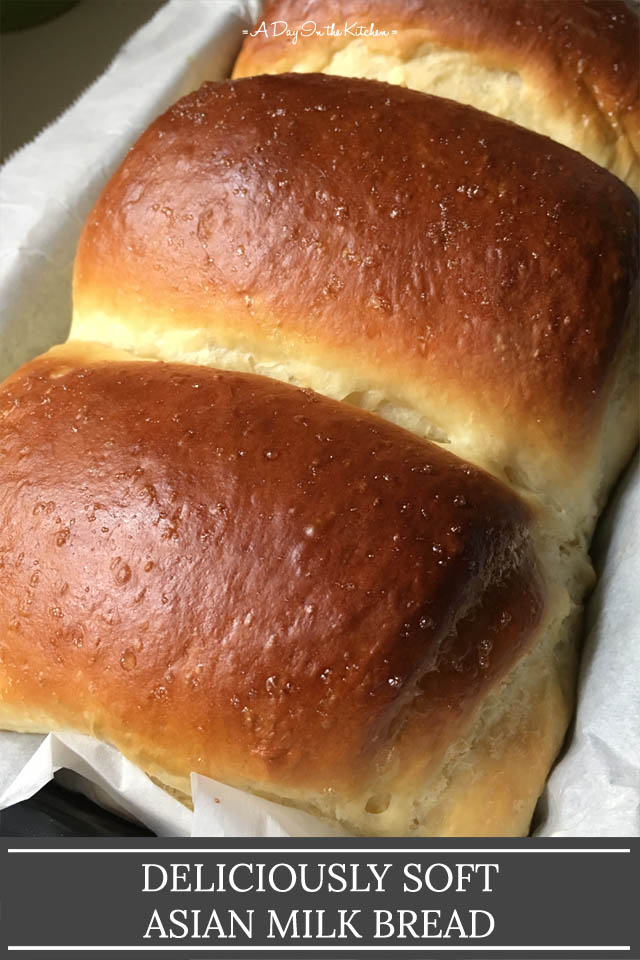 A brown loaf of bread in a paper lined baking pan, the words deliciously soft Asian milk bread on the bottom