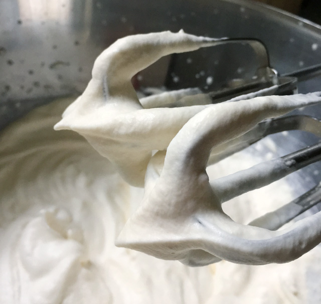 Close-up of mixer beaters with stiff whipped cream peaks