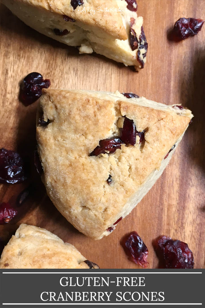 Cranberry scone wedges and dried cranberries on a brown wood surface, the words gluten-free cranberry scones on the bottom