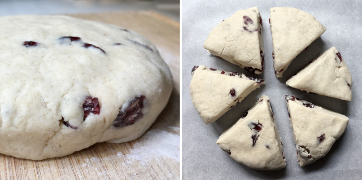 A disc of cranberry scones dough on a wooden cutting board, 6 wedges of cranberry scones on parchment paper