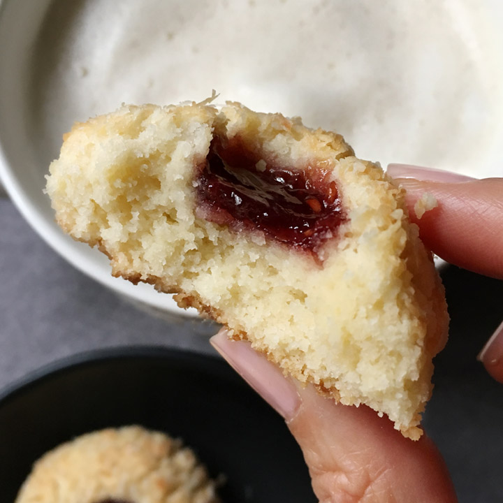 Closeup of a hand holding a jam cookie with a bite taken out