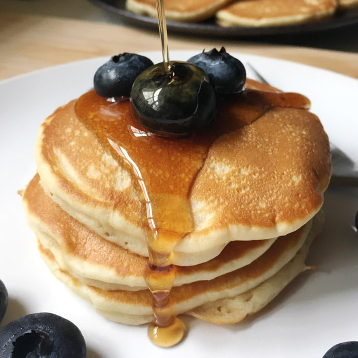 Syrup being poured over a stack of pancakes and blueberies on a white plate