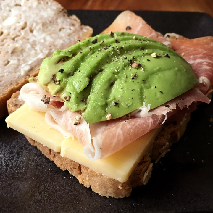 Slices of green avocado, pink ham, and white cheese on a slice of bread on a black plate