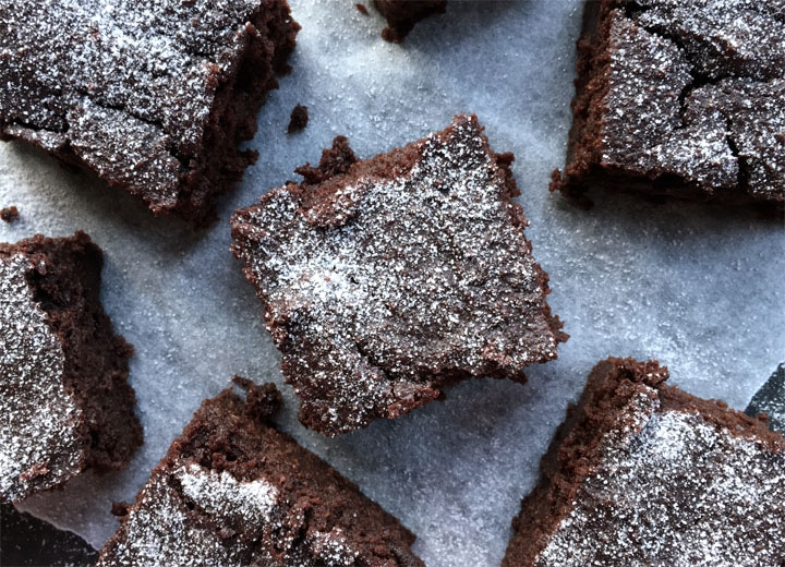 Square pieces of chocolate cake dusted with white powdered sugar