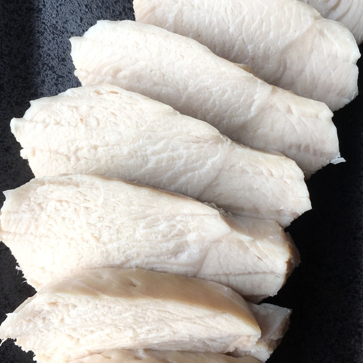 Several slices of white chicken breast meat on a black plate