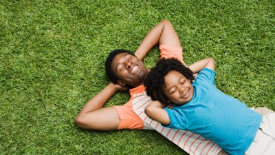 father and son lying in the grass, daydreaming, to channel ADHD creativity and gifts
