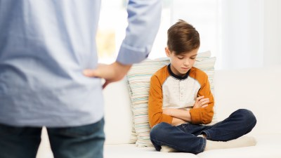 A boy with ADHD looks dejected while his ADHD father disciplines him.