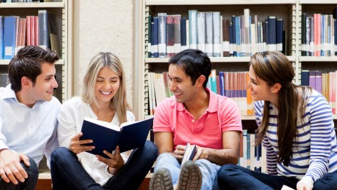 Four college students with ADHD study together in the library.