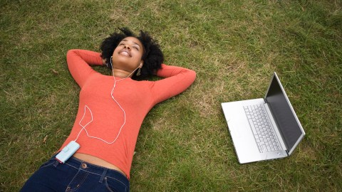 College student laying on the grass, listening to calming music to stay relaxed