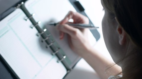 A woman writing in her planner on what she has been doing with her time, a good way to keep track of time spent and get things done.