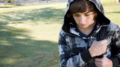A boy with social anxiety disorder looks at the ground