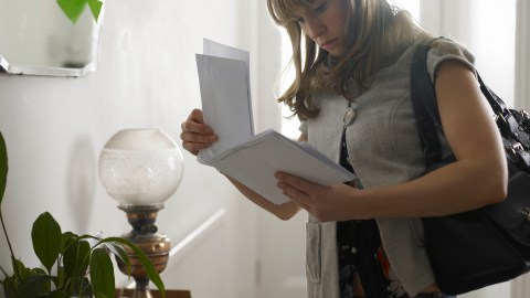 A woman sorts her mail, avoiding unexpected surprises and helping to simplify her life.