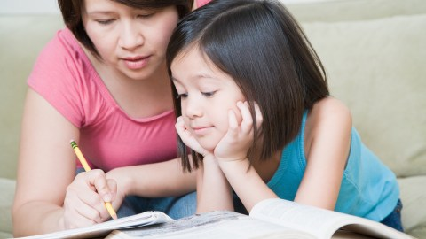 A mother and daughter work on math problems together, relieving homework stress with teamwork.