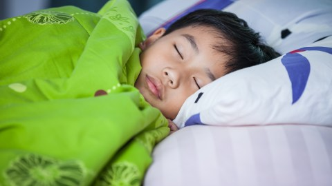 A boy with ADHD asleep in bed