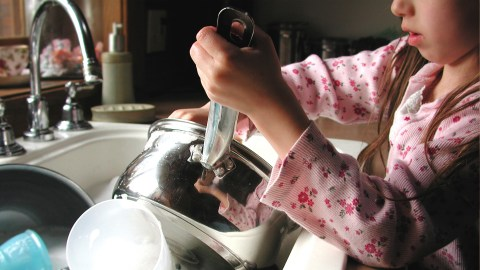 A girl with ADHD washes the dishes, one of the chores on her to-do list