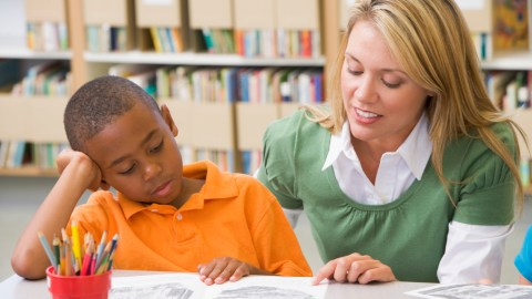 A teacher works with a student with ADHD, which is often misdiagnosed as a learning disability.