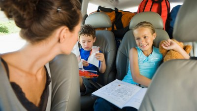 A girl with ADHD works on her homework in the backseat as part of her daily routine.