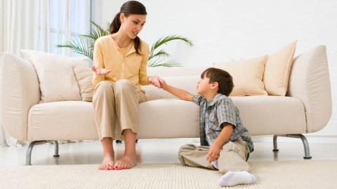 A mom sits on the couch and talks about anger management for kids with her son sitting on the floor