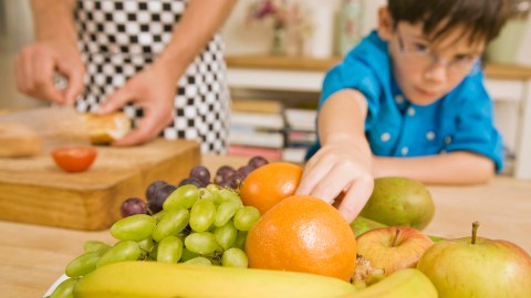 A boy with ADHD reaches for a piece of fruit.