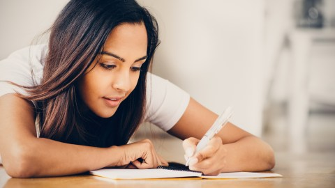 A teen girl with ADHD studying her notes to assess how well she's learning