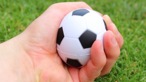 A boy squeezes a mini-soccer ball, his fidget to stay focused in class