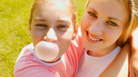 A girl with ADHD blows a bubble of chewing gum and hugs her friend
