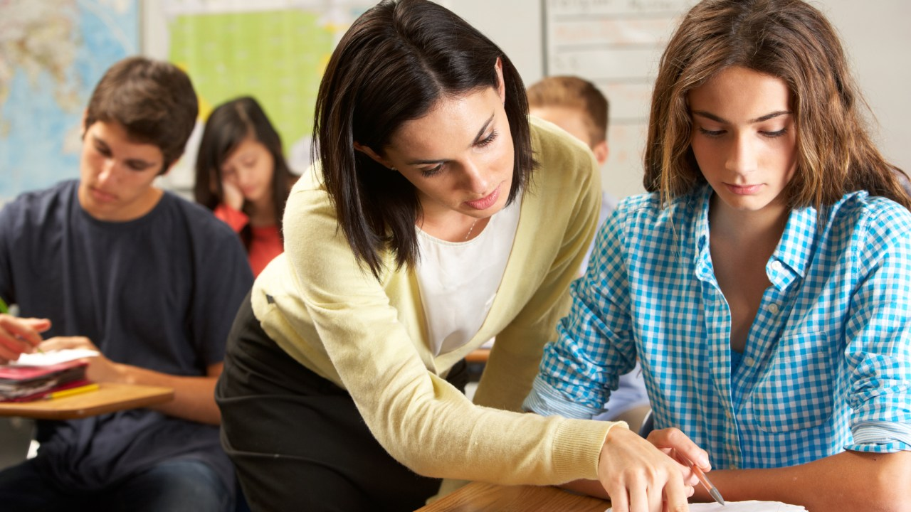 A teacher helps a girl who is struggling in class. She may have a learning disability.