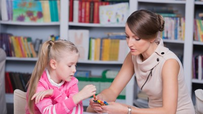 A therapist evaluates a child for symptoms formerly associated with Asperger's syndrome.