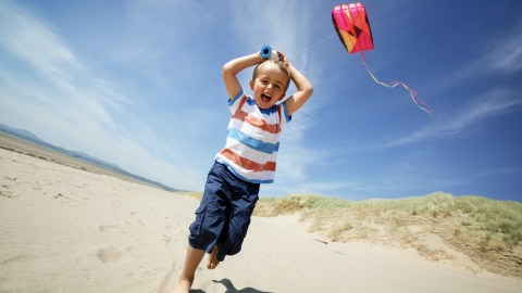 Boy running with kite during the summer, enjoying his empty schedule