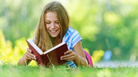 A young girl avoids summer learning loss by reading in the park during the summer.