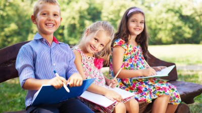 Three children avoid summer learning loss by reading together on a bench