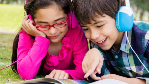 Two children with headphones reading together to avoid summer learning loss