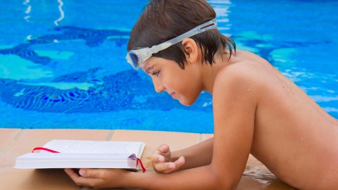 A boy reading a book by the pool during the summer to prevent learning loss