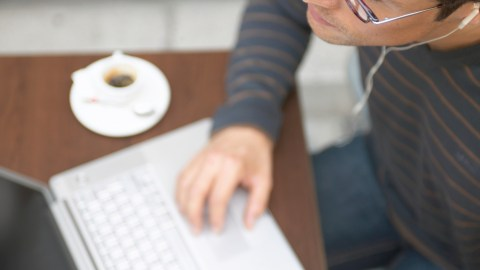 A man with ADHD is putting things off by browsing the internet on his laptop at a cafe.